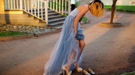 luxúria : Beautiful girl in silver and blue dress takes off high heeled shoes and puts on flats sranding on path.