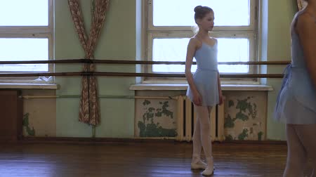 third world : Girl in blue ballet suit stands in third position wating for exercise to start and listen to choregrapher durin ballet lesson.