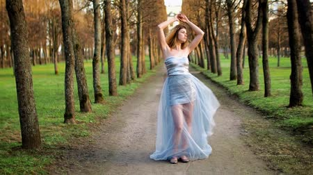 столбцы : Attractive girl with black brows and curly hair in silver and blue dress poses standing on path of parkway during photoshoot. Стоковые видеозаписи