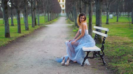 luxúria : Attractive girl in silver and blue dress sits on bench in parkway posing, making faces and having fun during photo shoot, then photographer approaches her. Sideview