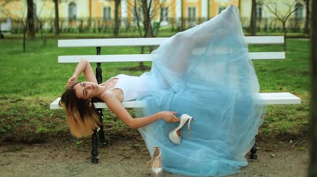 photoshoot : Attractive girl in white and blue dress lies on bench with bare feet and handles high heeld shoes posing during photo shoot.