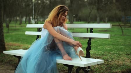 spona : Attractive girl in white and blue dress sits on bench in parkway putting on high heeled buckle shoes and talks during photo shoot. Dostupné videozáznamy