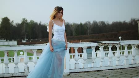 luxúria : Attractive skinny girl in white and blue dress stands near white stone balustrade with flowerpot posing and approaching photographer during photo shoot. Stock Footage