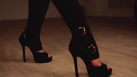 striptérka : Womans legs in black stockings and stipper shoes move while dancing.