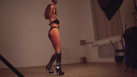 стриппер : Female dancer in black bodysuit, gloves and glittering high-heeled boots dances go-go. Bottom view. 2