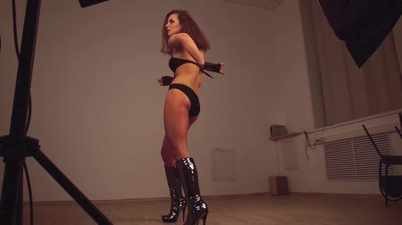 divas : Female dancer in black bodysuit, gloves and glittering high-heeled boots dances go-go. Bottom view. 5