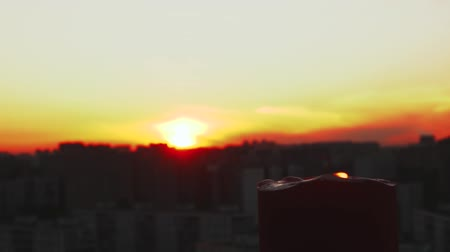 tragédia : Candle flame bickers in right corner behind sunset and big city towers.