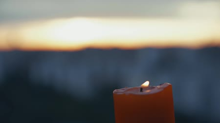 eterno : Candle light bickers in right corner behind blurred view of sunset.
