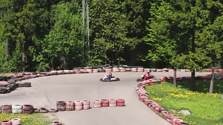 roadster : Boy and father drive karting cars. Move slowly because father will not walk away his son. Stock Footage