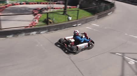 roadster : Boy in blue suit drives karting car on track.