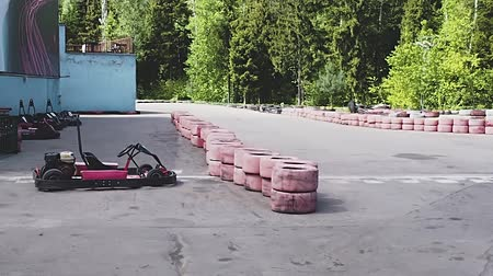 motorcar : Boy in red suit drives karting car on track and waves his hand crossing finish line.