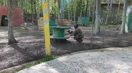 paintball : Man in protective uniform and mask sits in ambush with gun then stands up to look for enemy playing paintball Stock Footage