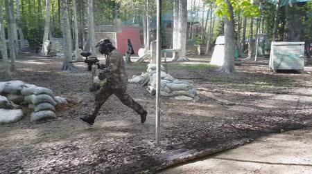 paintball : Man in protective uniform and mask with gun in right hand runs playing paintball. Slow motion