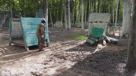 paintball : Paint ball player stands behind shield hiding from enemies.