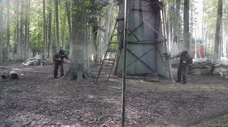 paintball : Paintball players run and shoot at each other and then hide behind tree and shield Stock Footage