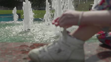 Blur of girl sitting near fountain and lacing sport shoes. Slow motion view 動画素材