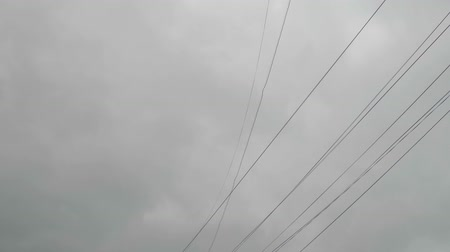 karartmak : Electrical wires sway during stormy weather with grey sky behind