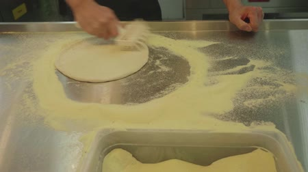 baking dishes : Mans hands roll dough with studded roller. Flour scatters around.