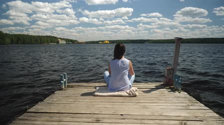 koncentracja : Young woman sits in lotus pose on old wooden pier throws up her hands.