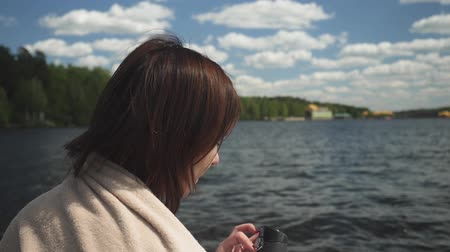 carrancudo : Sad brunette in blanket sitting and drinking from a mug on the background of water and forest
