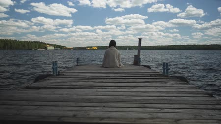 mesafe : Brunette in plaid sad sitting on an old wooden pier and looks out at the water and forest in the distance.