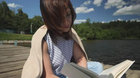 roman : Young brunette woman in a blanket sits with her back to the water forest and reads a book