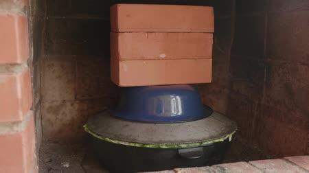 basmati : Cauldron full of food stands in a stove covered with a lid and bricks on top Stock Footage