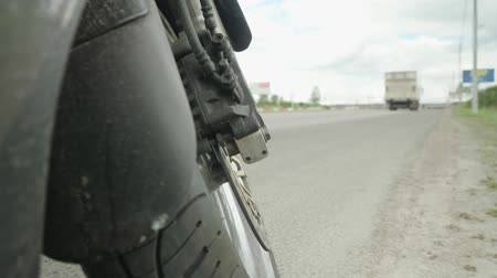 stopping : Black touring motorcycle is standing on the sidewalk. Bottom view from the front wheel to the forward road