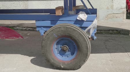 hull : Old blue trailer wheel loaded with a yacht moves along a concrete surface