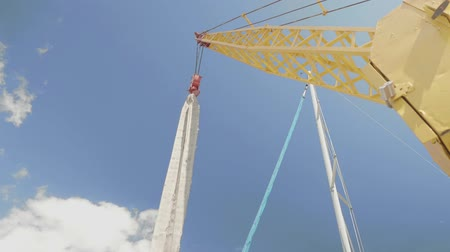industrial fishing : Yellow crane for lowering or raising yachts. Against the blue sky hang the prepared strip