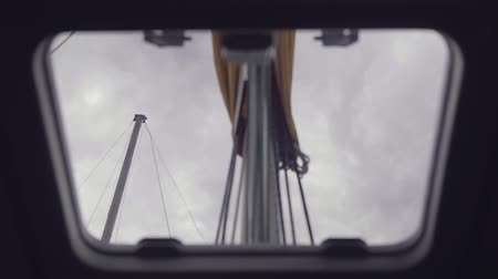 строгий : View from the hatch of the yachts cabin on the mast against the background of clouds.