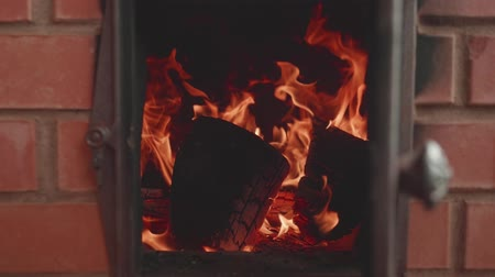 coque : Spirts of flame in fireplace. Mans hand closes door of fireplace. Slow motion view
