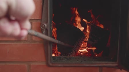 coque : Mans hand stirs fire with poker. Fire flame becomes cleare. Slow motion view. Stock Footage
