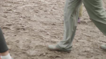 grime : Legs of people in rubber boots walking in mud after rain. Slow motion Stock Footage