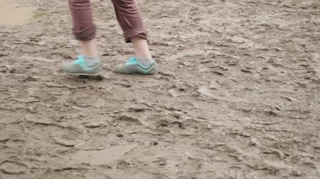 風化した : Guy in blue sport shoes walking on muddy ground.Slow motion 動画素材