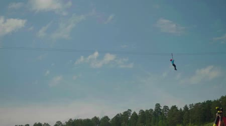 zipline : View of girl riding zip line on sunny summer afternoon with blue sky behind