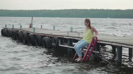 dangle : Brunette in yellow tank and blue jeans sit on wooden pier and splashes water with leg Stock Footage