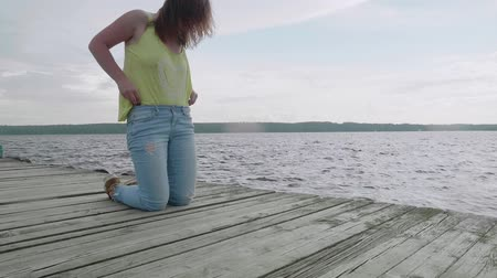 dangle : Girl stands on knees and adjust clothes on wooden pier Stock Footage