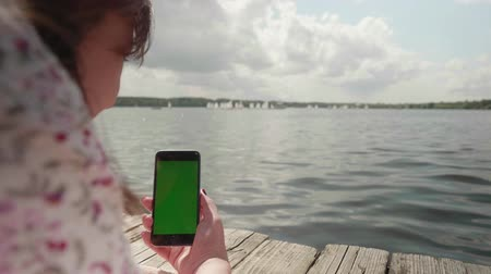 dragging : Girl lies on wooden pier on river and looks at green screen of smartphone and sсrolls it
