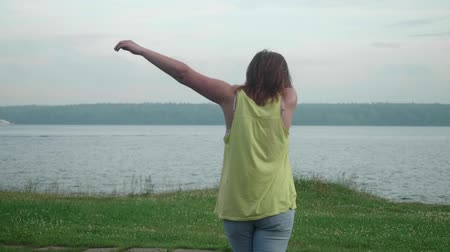 dab : Girl stands on bank of river and takes dab pose