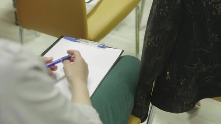 lugares sentados : View of girls hands holding writing pad and pen on laps
