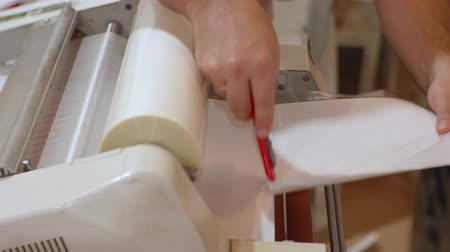 nakladatelství : White male working with roll laminator.