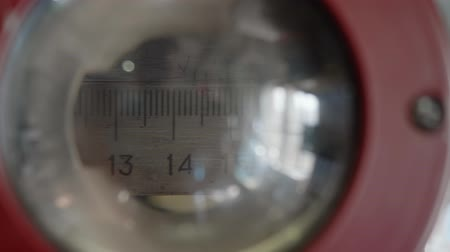 değil : Measuring ruler of old machine is moved upwards. View through lens