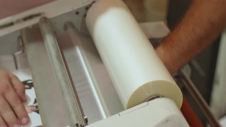 photocopier : Hands of caucasian man run a roll laminator during its work Stock Footage