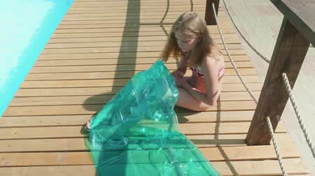 inflável : Young long-haired blonde puffs up the mattress by the pool Vídeos