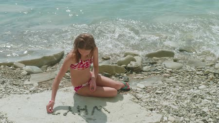 слово : Young blonde girl in bathing suit sits alone on stony beach and makes out the stones of question Why