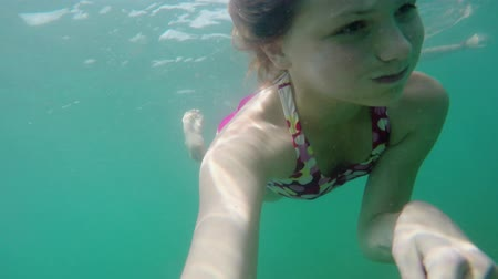 mermaid : Young blonde girl in swimsuit swims under water on camera, Underwater shot