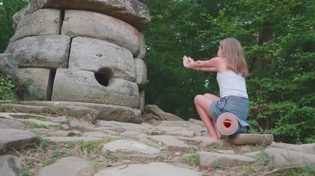 mito : Young caucasian blonde teenager sits opposite and extends her hands to an ancient dolmen. Left side view