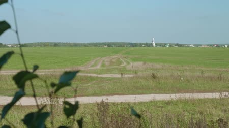 ветреный : View of church, forest and large green field with country road