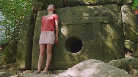 mitolojik : Young caucasian blonde girl stands in reverie with an ancient dolmen Stok Video